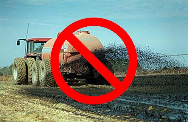 Truck spewing disgusting sewage sludge on a farm field.